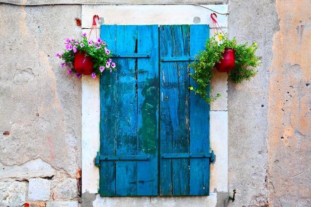 Oud pittoresk raam met luiken en bloempotten
