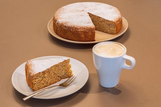Oud receptcake gemaakt van amandelen en droog brood (antica torta alle mandorle e pane) met een kopje cappuccino