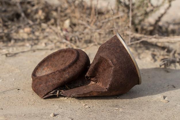 Oud roestig blikje buiten, roestig blik liggend in het veld, afval