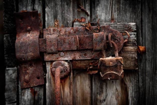 Oud roestig hangslot op deur
