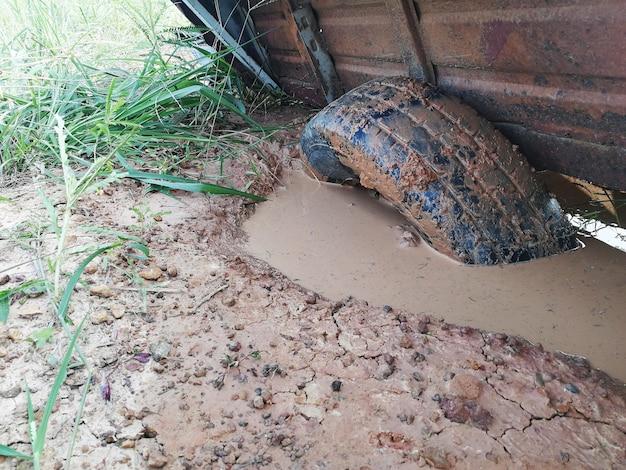 Oud rubberwiel in modderig gat op grondgrond