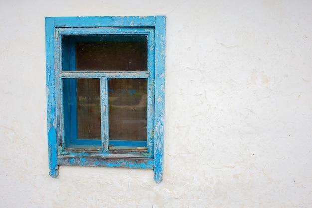 Oud rustiek venster met een blauw kader op een witte muurachtergrond