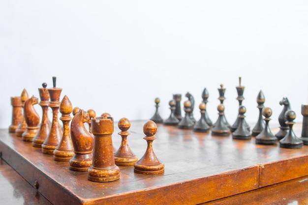 Oud schaakbord met houten stukken.