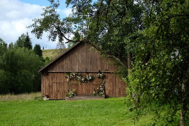 Oud schuur bruin blokhuis dat door groene bomen wordt omringd. de schuur is versierd met bloemen en groen. helder beeld van het landschap.