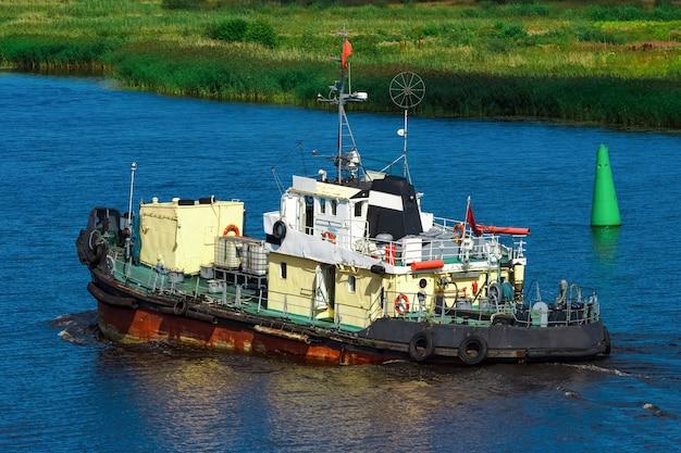 Oud sleepbootschip dat zich naar de vrachtterminal verplaatst. industriële service