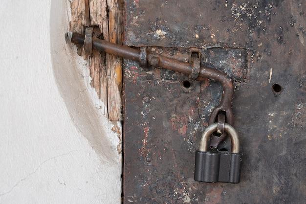 Oud slot op een stalen zwarte sjofele deur
