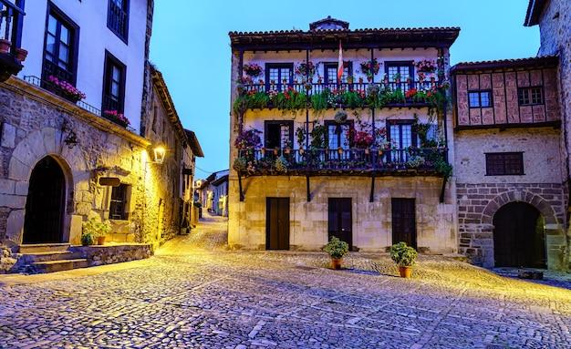 Oud stadsplein met oude huizen en houten balkons met bloempotten.