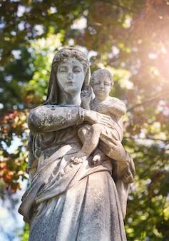 Oud standbeeld van de maagd maria met jezus christus in het zonlicht