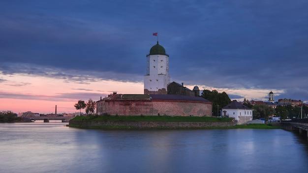 Oud stenen kasteel op het eiland in vyborg bij zomerzonsondergang