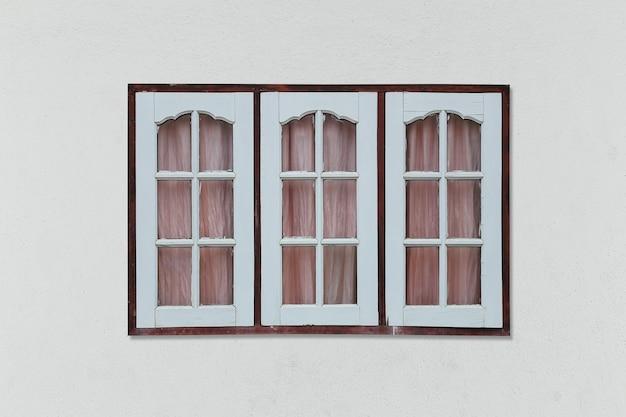 Oud uitstekend houten venster op grijze muurachtergrond.