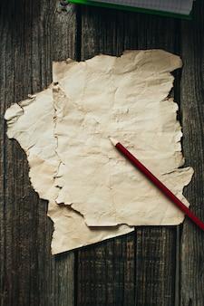 Oud vel papier op oude houten muur, liggend naast een rood potlood