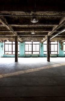 Oud verlaten pakhuis bij fabriek met lange gang en grote vensters