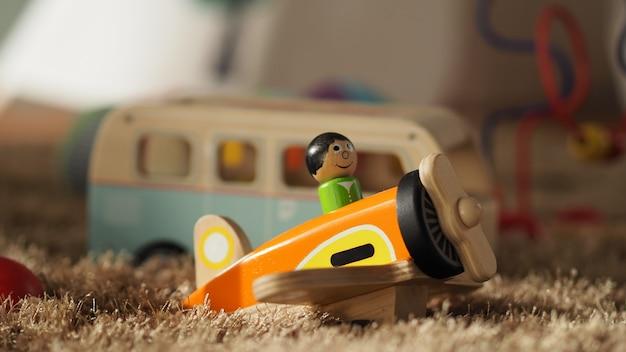 Oud vintage houten speelgoed voor baby's of kinderen op lichtbruin tapijt met een vliegtuigbusbal airplane