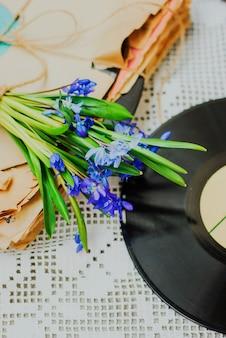 Oud vinylverslag en vroege de lentebloemen op witte achtergrond.