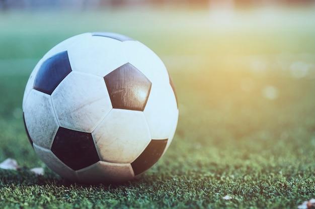 Oud voetbal op het groene kunstmatige grasgebied - de concurrentie van het voetbal of van de voetbalspel