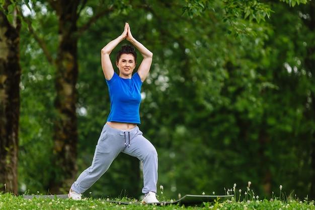 Oud wijfje dat yogaoefening in park doet. senior vrouw beoefenen van yoga outdor