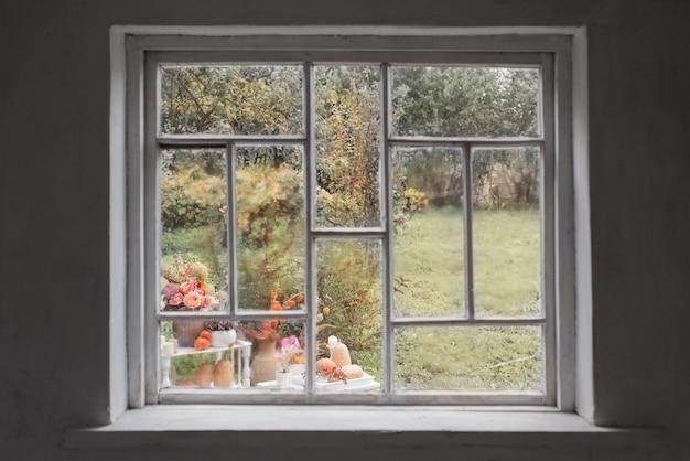 Oud wit houten raam met regendruppels en herfstdecor in de tuin