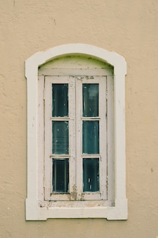 Oud wit venster op een lichtrose muur