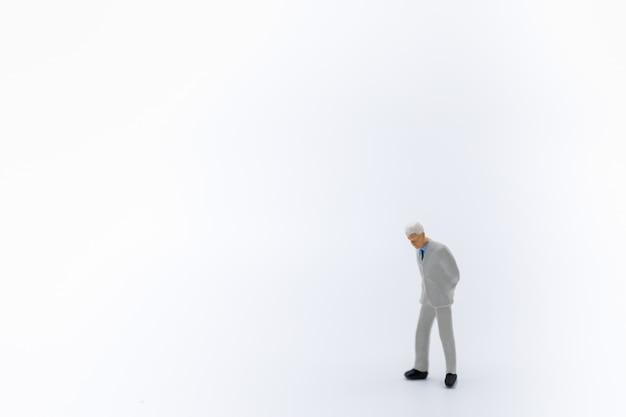 Oud zakenman miniatuurcijfer dat en zich op wit bevindt loopt.
