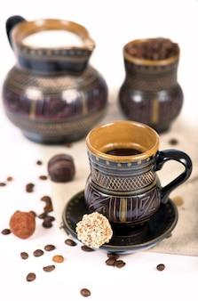 Oud zwart aardewerk, koffiebonen, snoep en een kopje drank