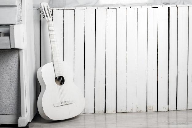 Oude akoestische gitaar leunend tegen de witte houten muur