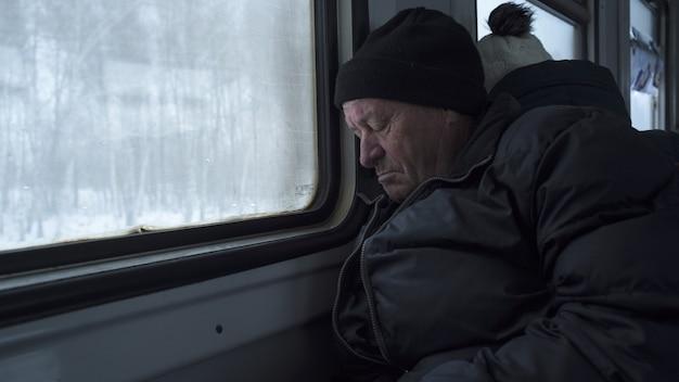 Oude arme russische oude man die in de trein slaapt
