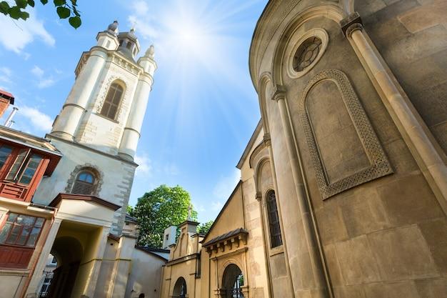 Oude armeense kerk in lviv city (oekraïne) en zonneschijn in blauwe zomerhemel summer
