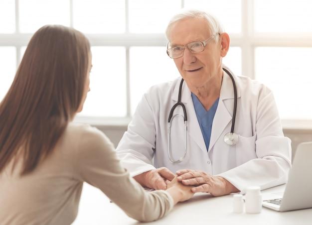 Oude arts in witte medische jas en bril.