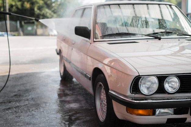 Oude auto die met waterslang wordt gewassen