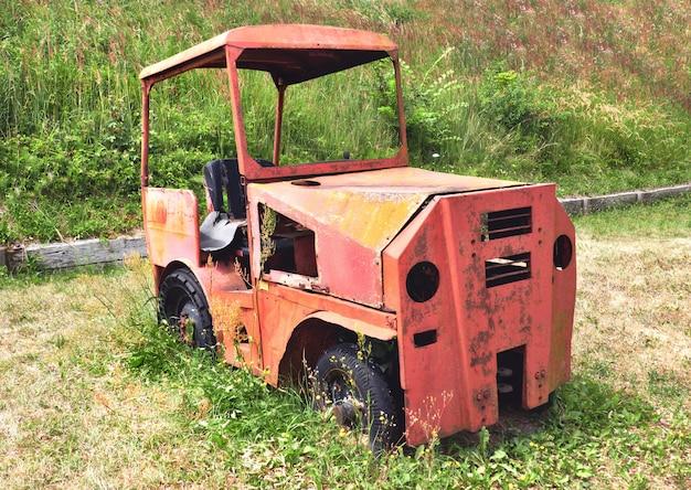 Oude auto, gesloopt en roestig, op een groen gazon