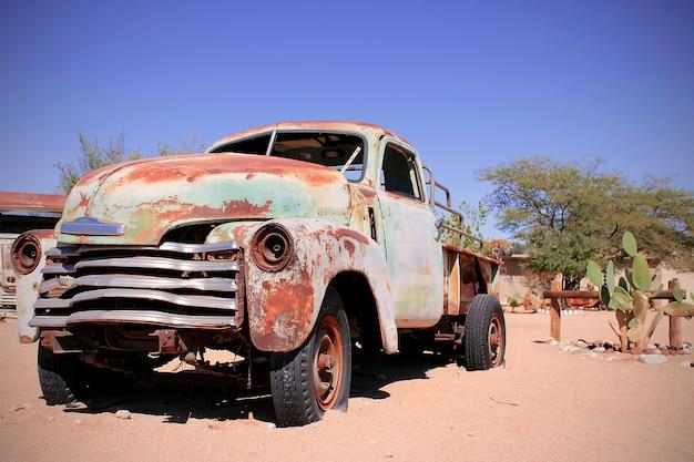 Oude auto in het zandlandschap