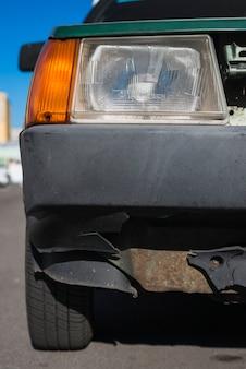Oude auto met gebroken bumper