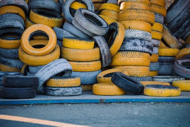 Oude autobanden, geverfd in gele en witte kleuren, liggen in de hoop. muur van gele autobanden.