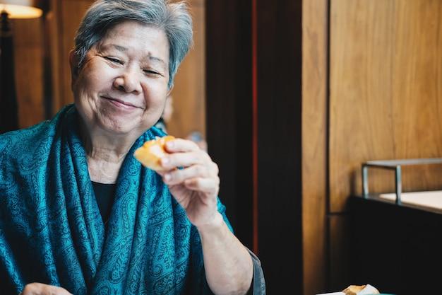 Oude aziatische bejaarde hogere oudere vrouw die brood eet bij restaurant