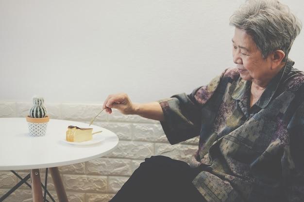 Oude aziatische bejaarde hogere oudere vrouw die kaastaart eet bij restaurant.