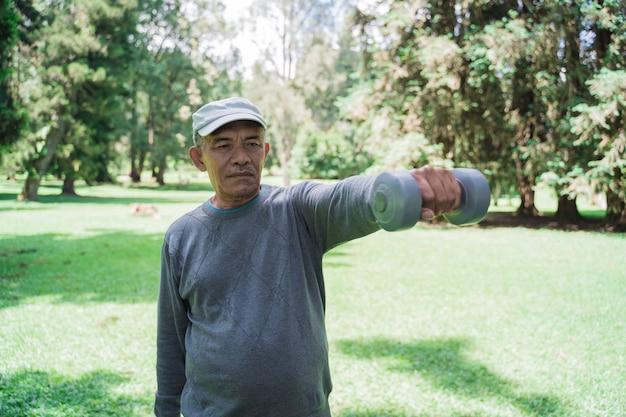 Oude aziatische mens die dumbell in het park gebruiken