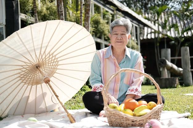 Oude aziatische oudere senior oudere vrouw met picknick in de tuin. volwassen pensioen levensstijl