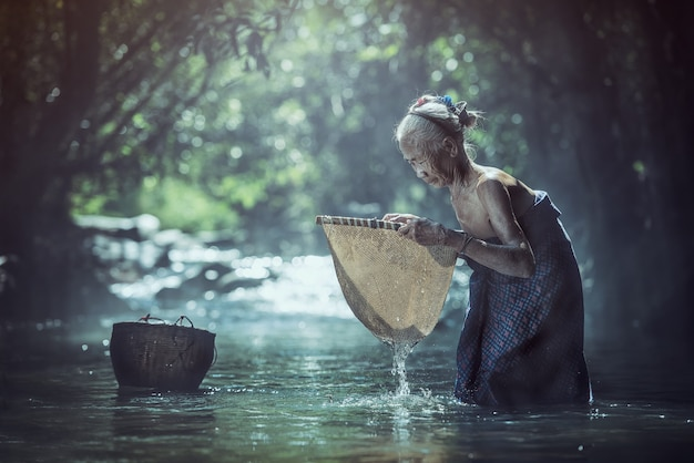 Oude aziatische vrouw die in kreek, het platteland van thailand werkt