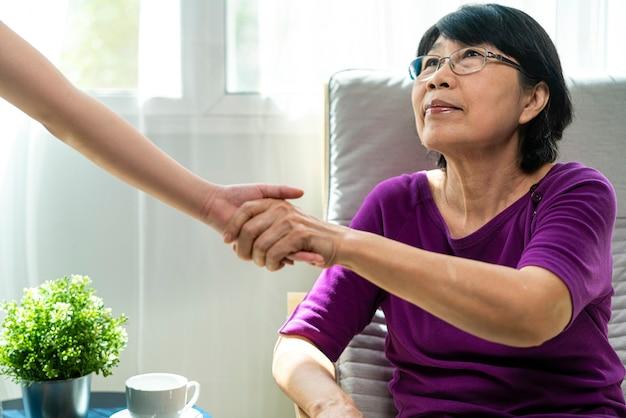 Oude aziatische vrouw houdt de hand van kinderen om op te staan vanuit de fauteuil in de woonkamer, een aziatisch familie- en relatieconcept