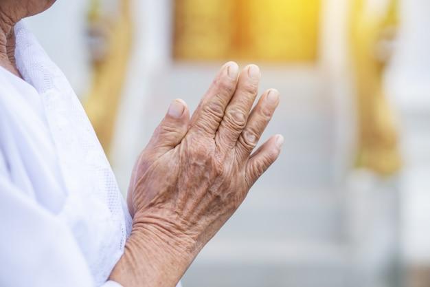 Oude aziatische vrouwelijke hand die in tempel bidt