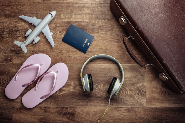 Oude bagage, koptelefoon, flip-flops, vliegtuigbeeldje, paspoort op houten vloer