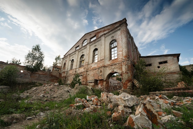 Oude bakstenen gevel van het gebouw uit de 19e eeuw, verwoest door alle wind, onder de blote blauwe hemel.