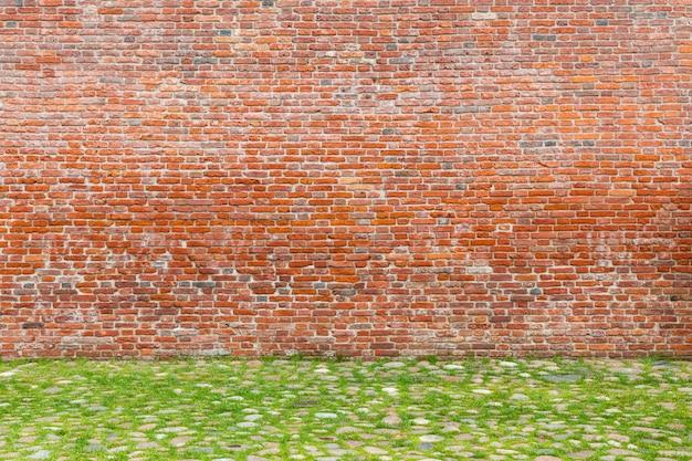 Oude bakstenen muur en geplaveide bestrating begroeid met gras