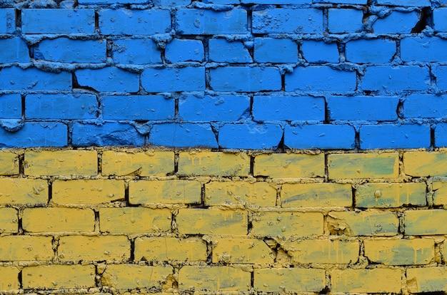 Oude bakstenen muur geschilderd in de kleuren van de oekraïense vlag