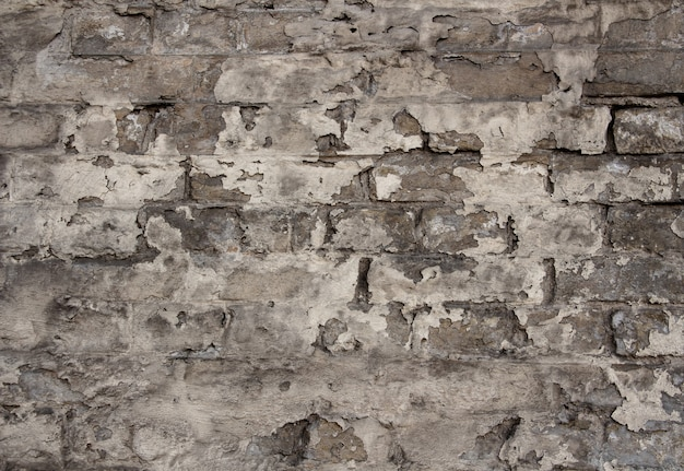 Oude bakstenen muur met afbladderende verf, sepia kleur, gestructureerde achtergrond