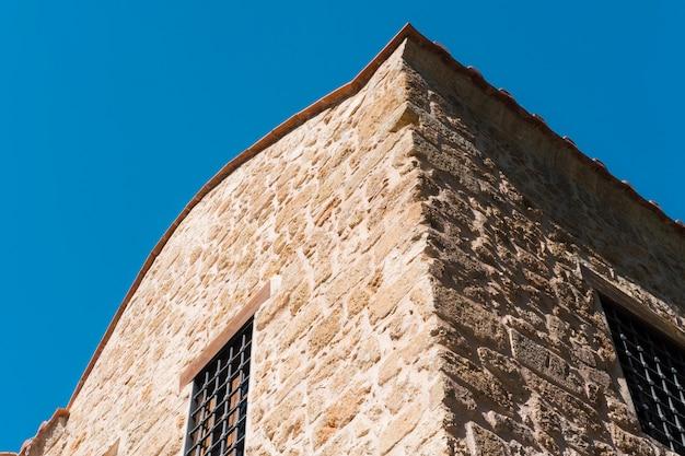 Oude bakstenen muur met rood betegeld dak