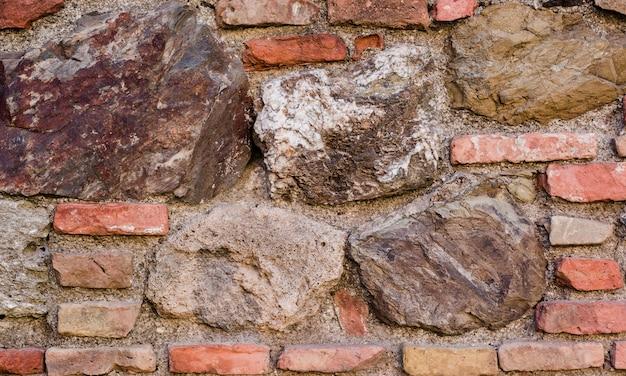 Oude bakstenen muur met stenen