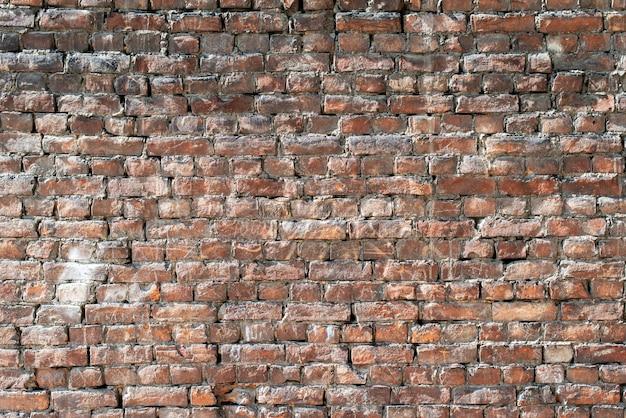 Oude bakstenen muur met uitpuilende delen als achtergrond.