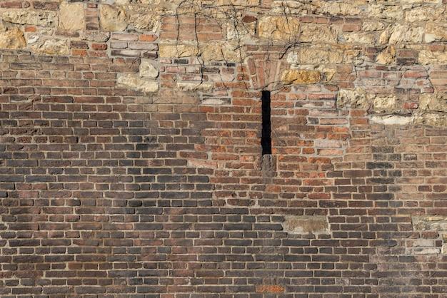 Oude bakstenen muur met wilde steen en een smalle patrijspoort