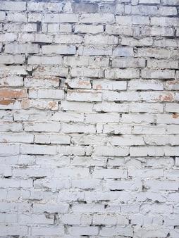 Oude bakstenen muur met witte verf achtergrondtextuur dicht omhoog